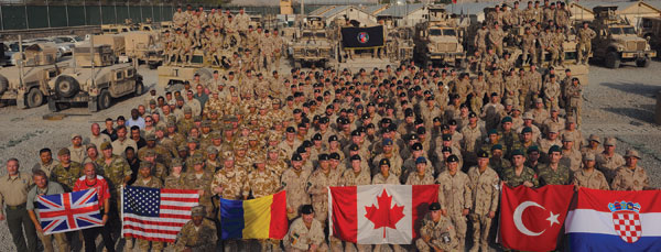 2013 – Coalition forces from the UK, the United States, Romania, Canada, Turkey, and Croatia pose for a group photo of the Canadian Contri­bution Training Mission – Afghanistan, at Camp Blackhorse, Kabul, during Operation Attention.