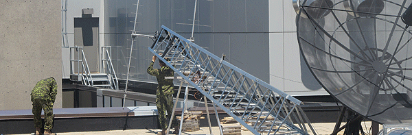 Students install the antenna for the RMCC Satellite Ground Station. This ground ­station is used to communicate with satellites in low Earth orbit using amateur radio bands.