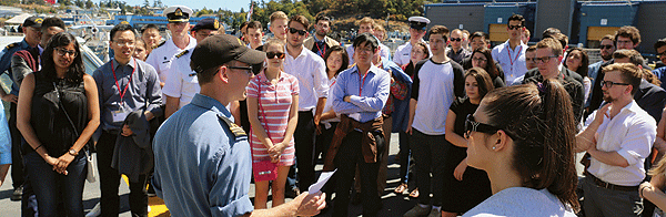 A member of the Royal Canadian Navy briefs students aboard HMCS Regina.