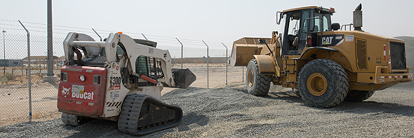 Mobile Support Equipment Operators use a bulldozer and bobcat to lay down gravel alongside the newly built fence at Camp Canada during Operation IMPACT in Kuwait on August 24, 2016.