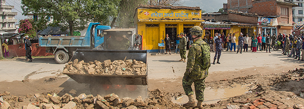 May 2015 – Combat engineers of the Disaster Assistance Response Team clear a road using a mini-excavator in the town of Sankhu, Nepal, after a 7.8 magnitude earthquake hit the area.